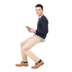 Handsome Asian guy sit and use pad