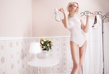 Sensual blonde woman posing in room.