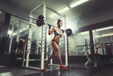 Fototapety Young sexy girl in the gym doing squat on smoke background