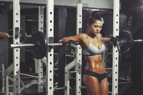 Woman resting after lifting barbell in gym - 67268855