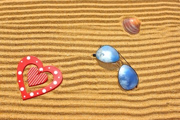 Sunglasses, wooden heart and seashell on the beach sand