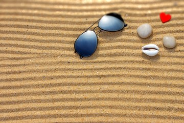 Sunglasses and  different objects on the beach sand