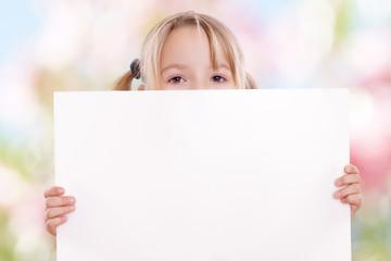 kleines Mädchen hält eine weiße Tafel