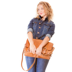 Denim fashion. College student girl in blue jeans holds bag