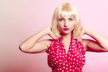 Portrait beautiful pinup girl in blond wig retro