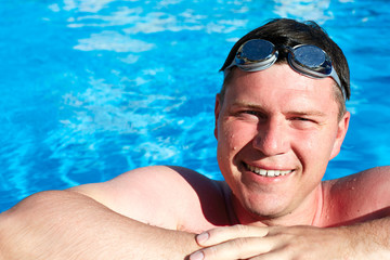 Happy smiling athletic swimmer wearing glasses at swimming pool