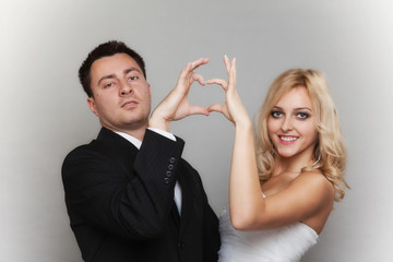 Portrait of happy bride and groom showing heart sign