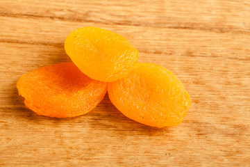 Dried apricots on wooden table background.