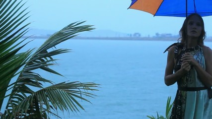 young woman on a tropical beach with umbrella in rainy season.