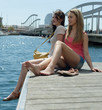 Couple of friends girls sitting near the bridge