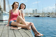 Two happy young women sitting on the berth