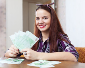 woman with many euro in home