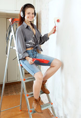 woman in headphones with roller on stepladder