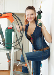 young woman in overalls with drill