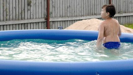 Boy swimming in inflatable pool in the yard