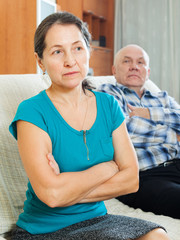 Upset mature woman against elderly husband