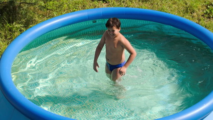 Boy having fun in outdoor pool on a hot summer day
