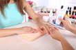 canvas print picture - Young woman is getting manicure in beauty salon, close-up