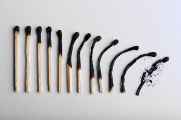 matches in different stages of burning, on color background