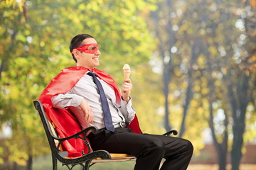Superhero enjoying an ice cream seated on bench