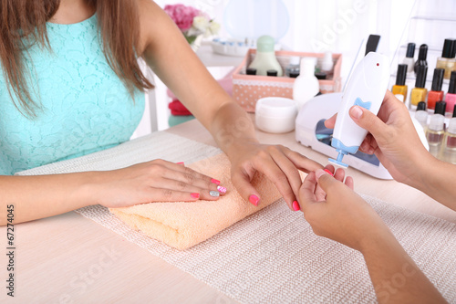 canvas print picture Young woman is getting manicure in beauty salon, close-up