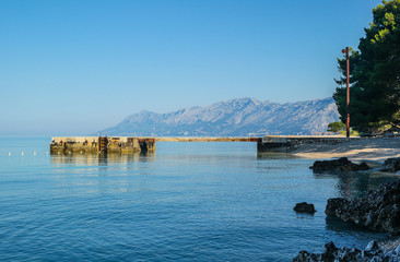 Small pier, mountains in the background,blue sea