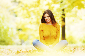Woman sitting on autumn leaves