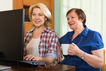 Two elderly women browsing web