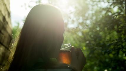 Girl drinking hot tea outdoor at sunset