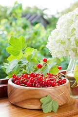 ripe red currants in wooden bowl and bouquet of white garden flo
