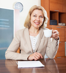 mature woman working with  documents at table in home