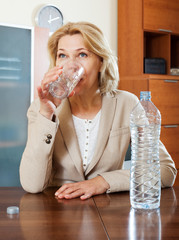Blonde mature woman drinking water