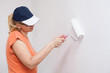 Woman painting white wall