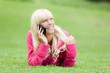 Junge Frau telefoniert auf der Wiese