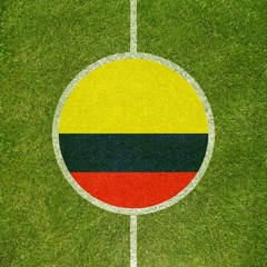 Football field center closeup with Colombian flag in circle