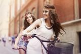 Boho girls riding a bike in city poster