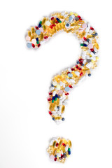 Pills as question mark on white background. Medical concept.