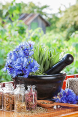 mortar with blue cornflowers and sage on windowsil