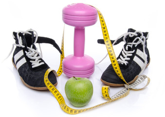 Pink dumbell, an apple and fitness shoes with a tape measure