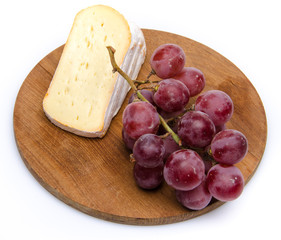 Soft cheese with grapes on a wooden board