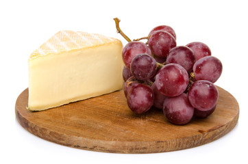 Cheese with grapes on a wooden board