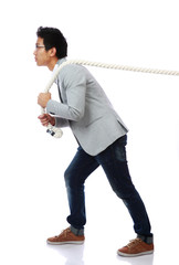Full length portrait of a man pulling rope over white background