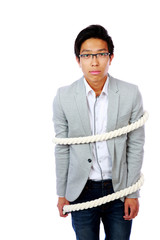 Young asian man tied with ropes isolated over white background