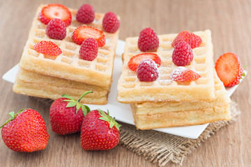 Delicious waffle with fresh berries for breakfast on wooden  bac