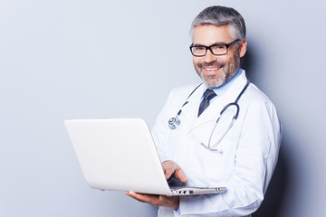 Cheerful doctor with laptop.