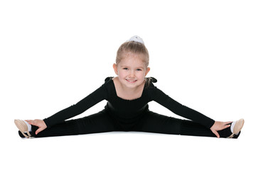 Pretty little girl performs gymnastic exercise