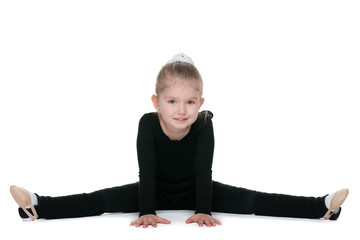 Small girl performs gymnastic exercise