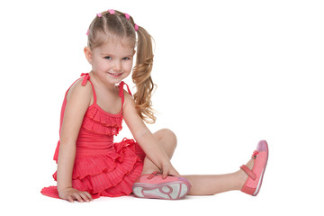 Happy little girl sits on the floor