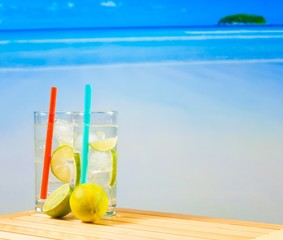 two glasses of cocktail with lime slice on blur beach