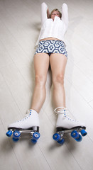 Woman laying on floor wearing quad skates